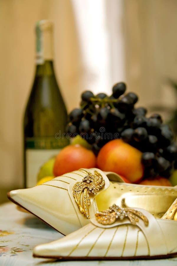 Brautfußbekleidung, Früchte und Weinflasche stockbild