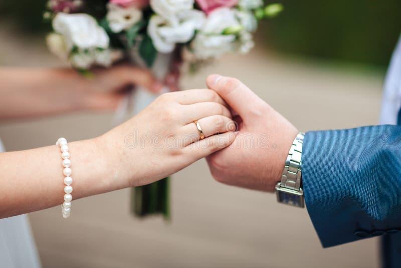 Brauthände mit Ring- und Hochzeitsblumenstrauß von Blumen, Jungvermählten halten Hände, Nahaufnahme stockbild