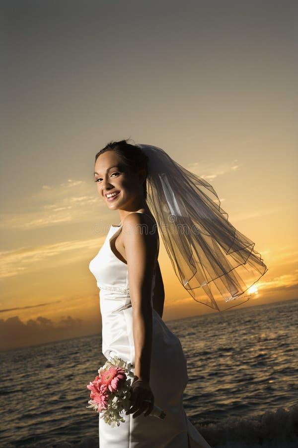 Brautholdingblumenstrauß auf Strand lizenzfreies stockbild