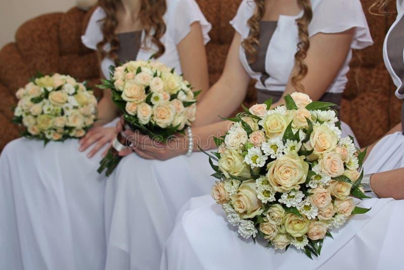 Brautjunfern, die Hochzeitsblumensträuße anhalten stockbilder