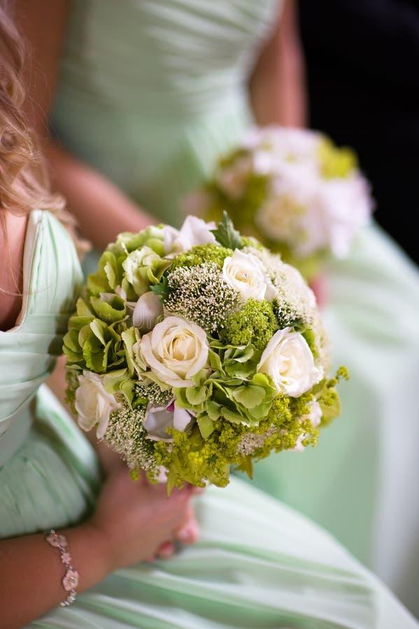 Brautjunfern im Grün mit Hochzeitsblumenstrauß stockbild