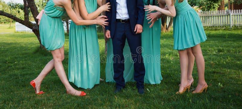 Brautjungfern, die Bräutigam auf ihren Händen im grünen sonnigen Park halten lizenzfreies stockfoto
