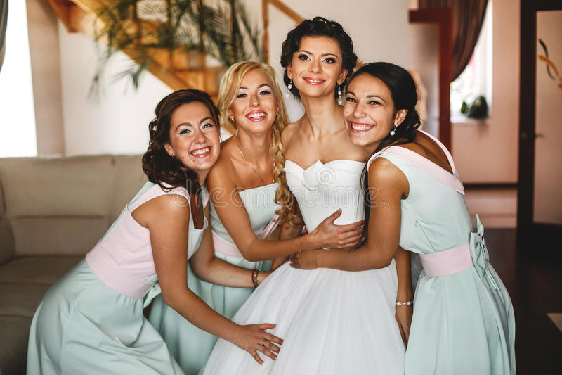 Brautjungfern, die eine reizend Braut umfassen stockbilder