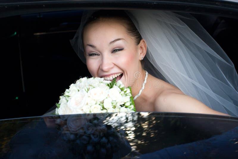 Brautlachen im Hochzeitsauto lizenzfreies stockfoto