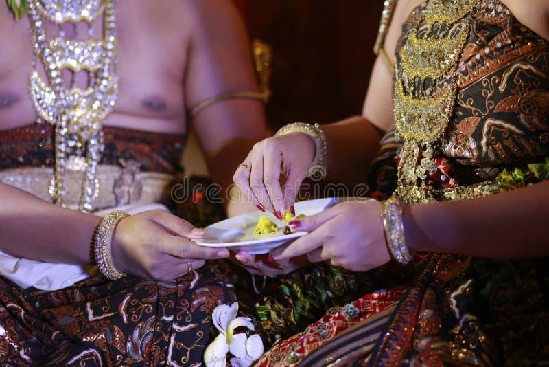 Brautpaar-Hand folgt Zeremonie, um sich in der Javanese-Hochzeit einzuziehen lizenzfreies stockbild