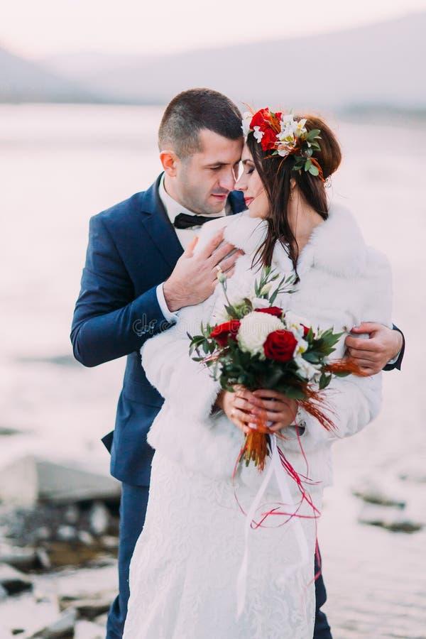 Brautpaare des glücklichen Jungvermähltens, die auf Kieselflußufer mit Forest Hills als Hintergrund sich halten stockbild