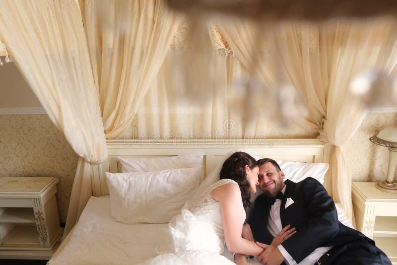 Brautpaare, die in Hotel ` s Raum umfassen lizenzfreie stockfotos