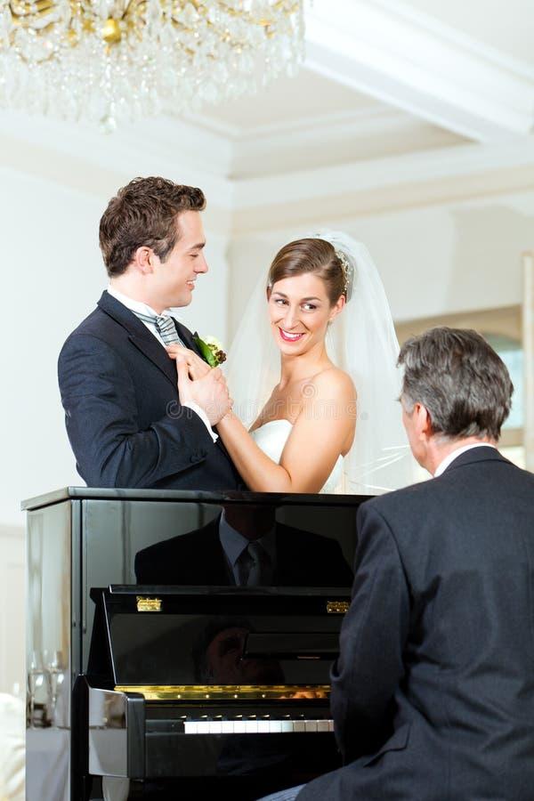 Brautpaare vor einem Klavier lizenzfreie stockbilder