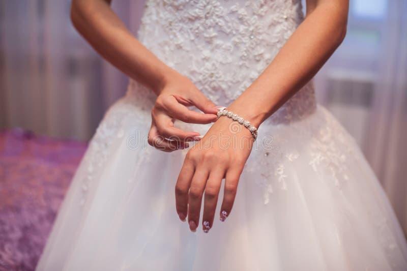 Brautvorbereitung, Braut, die auf Schmuck, Fokus auf Armband sich setzt stockbild