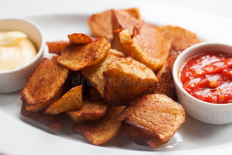 Bravas spagnoli di Patatas dei tapas dell'alimento di cucina, patata fritta con la salsa di aioli bianca del pomodoro rosso Fogli fotografie stock