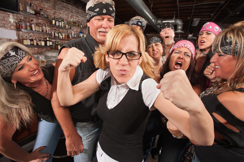 Brave Female Nerd with Biker Gang. Brave nerd lady with fists up among laughing biker gang stock photography
