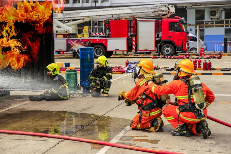 Brave firefighter using extinguisher and water from hose for fire fighting, Firefighter training with protective wear spraying stock photos