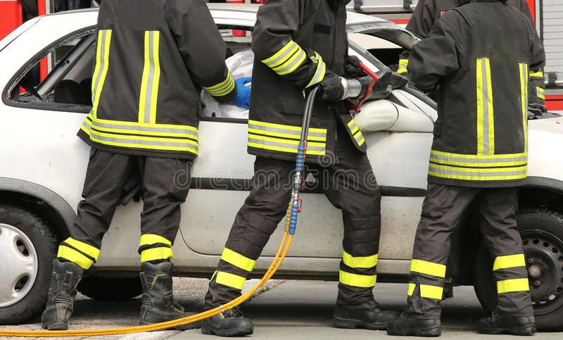 Brave firefighters relieve an injured after a road accident. Brave firefighters relieve an injured after an accident during a practice session in the fire royalty free stock photo