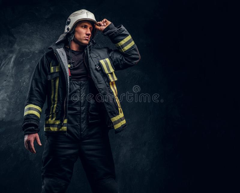 Brave fireman in a fire suit looking sideways and correcting the helmet with his hand stock photography