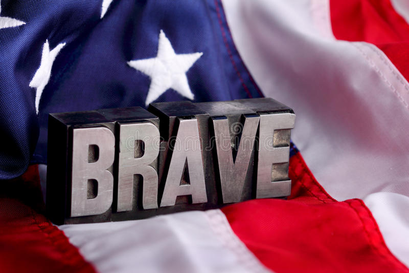 Brave on Flag. Letterpress blocks forming the word BRAVE letters on Stars and Stripes American flag background. shallow depth of field royalty free stock images