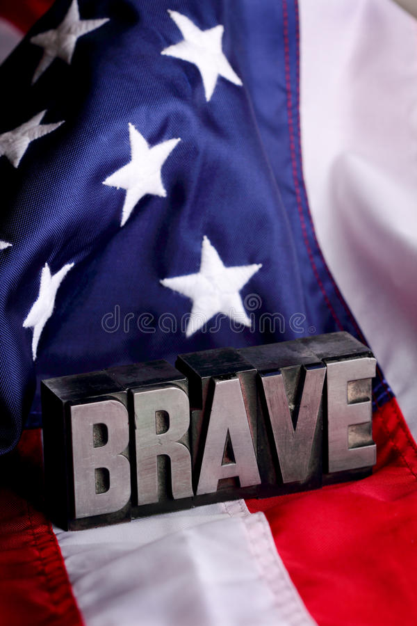 Brave and Flag. Letterpress blocks forming the word BRAVE letters on Stars and Stripes American flag background. shallow depth of field royalty free stock photography