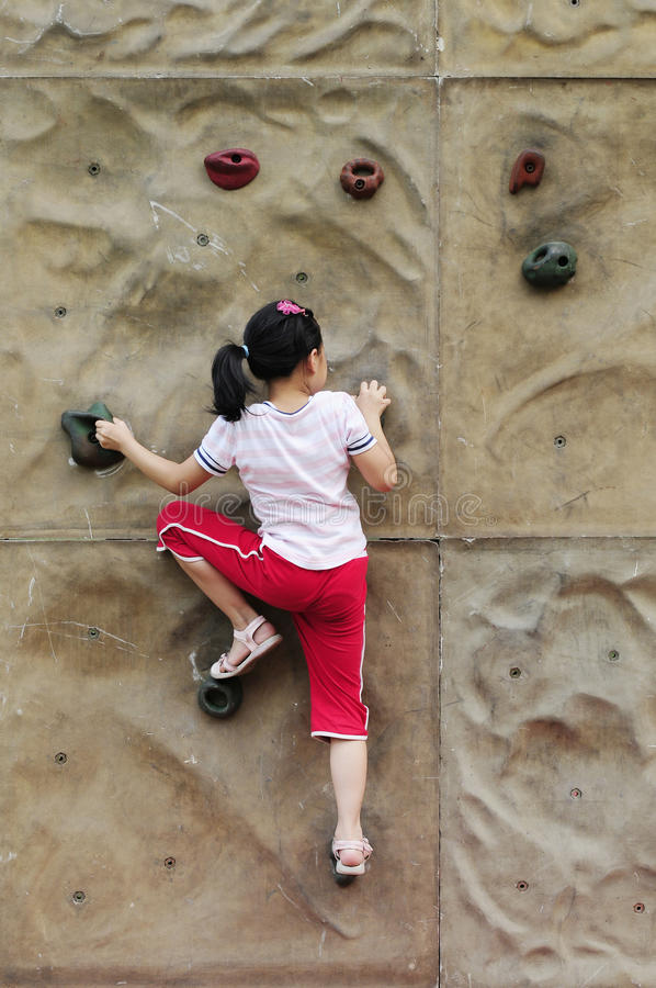 Brave Girl climbing on the wall royalty free stock photo