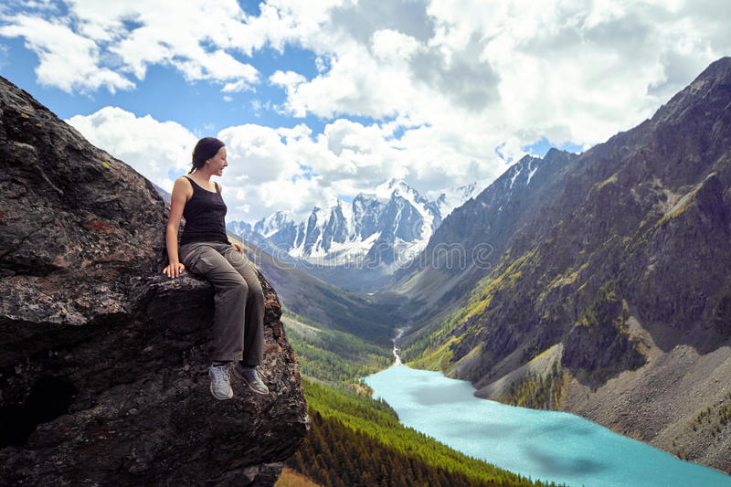 Brave girl conquering mountain peaks of the Altai mountains. The majestic nature of the mountain peaks and lakes. Hiking. In rugged places. Journey through stock image