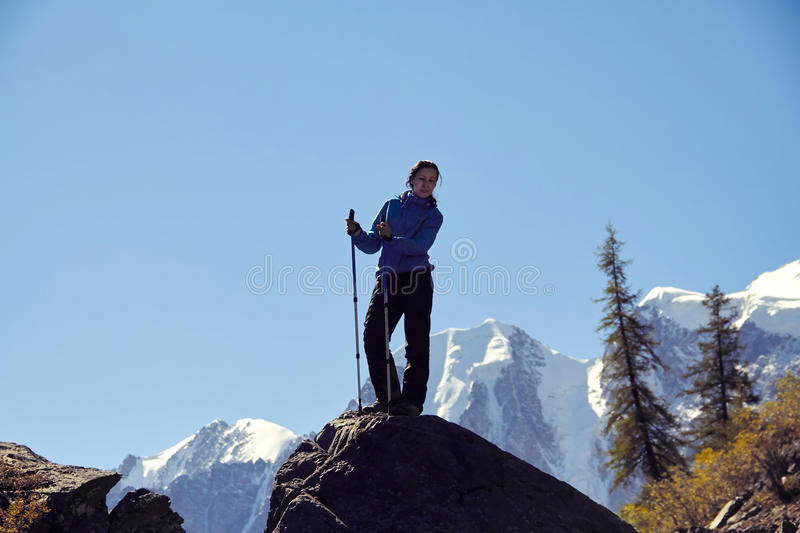 Brave girl conquering mountain peaks of the Altai mountains. The majestic nature of the mountain peaks and lakes. Hiking. In rugged places. Journey through royalty free stock images