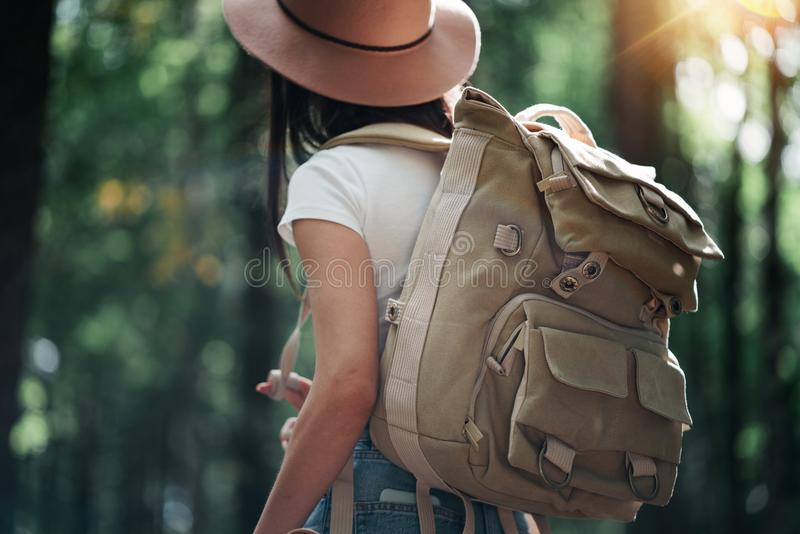 Brave hipster woman wearing backpack and hat traveling alone among trees in forest on outdoors royalty free stock image