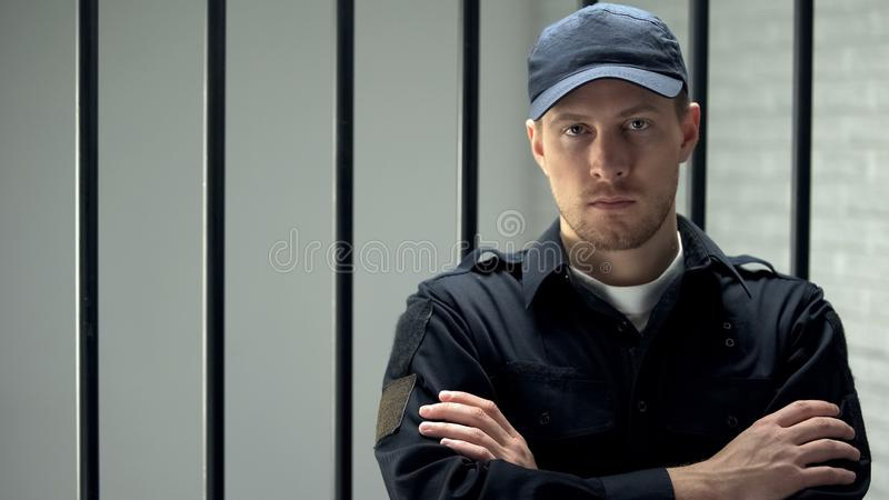 Brave jail guard looking at camera standing near cell, dangerous occupation. Stock photo stock image