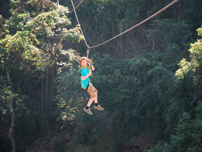 Brave little boy in helmet and harness zip lining at adventure park stock photography