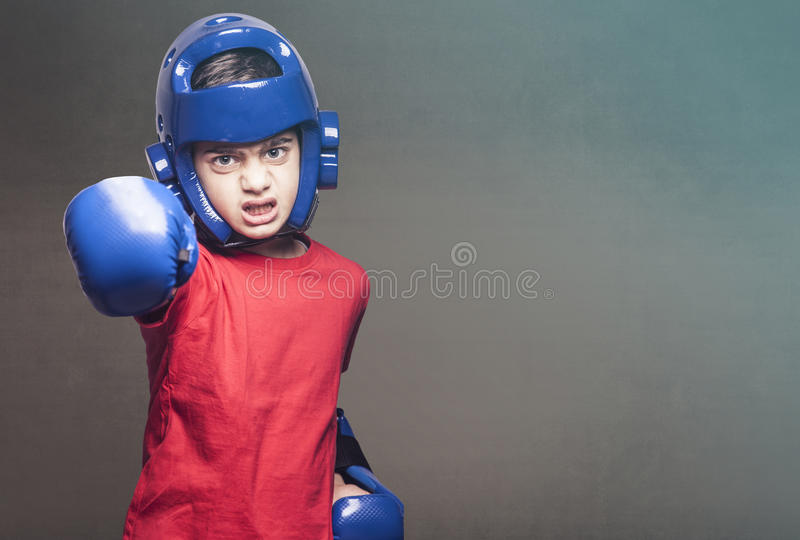 Brave little fighter. Determined little fighter wearing blue gloves and helmet royalty free stock photos