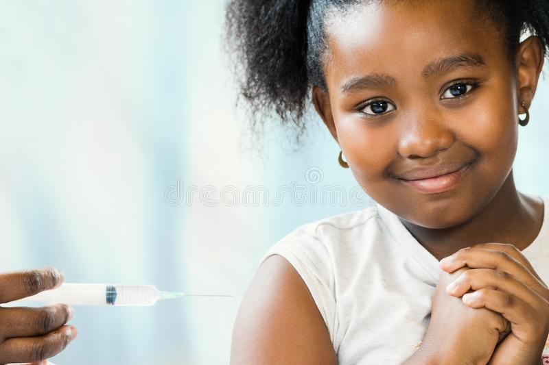 Brave little african girl at doctor`s practice. stock image