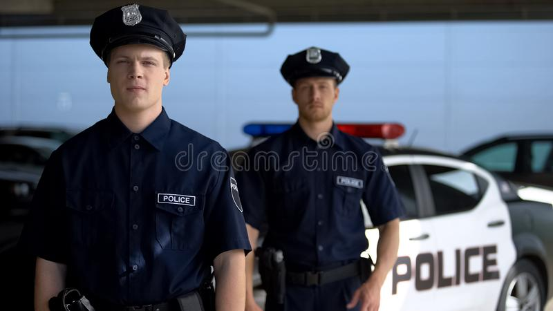 Brave male officers standing against squad car on background, important job. Stock photo royalty free stock photos