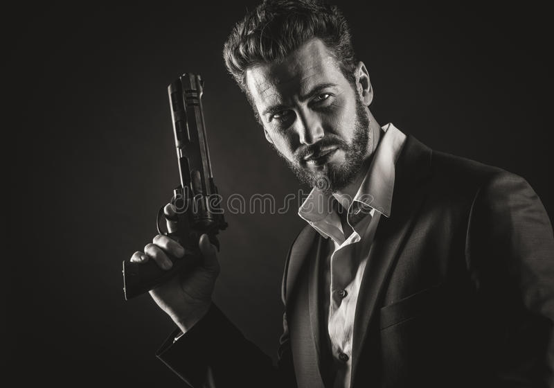 Brave man with dangerous weapon. Brave cool man holding a dangerous weapon on dark background stock image