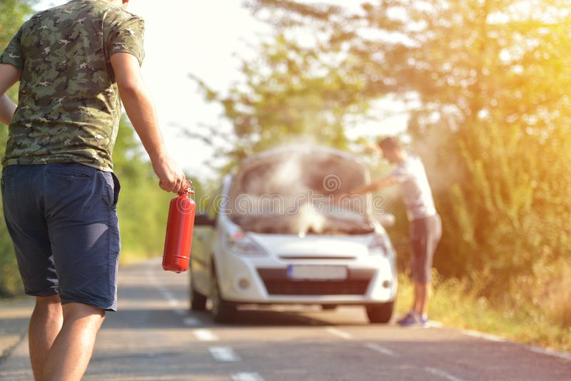 Brave man with fire extinguisher going to a car incident on the. Road with smoke on the engine stock images