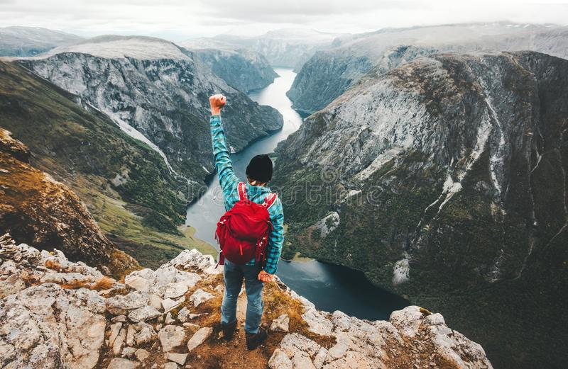 Brave Man traveling in Norway mountains standing on cliff. Active lifestyle weekend getaway adventure vacations success concept aerial view fjord landscape stock images