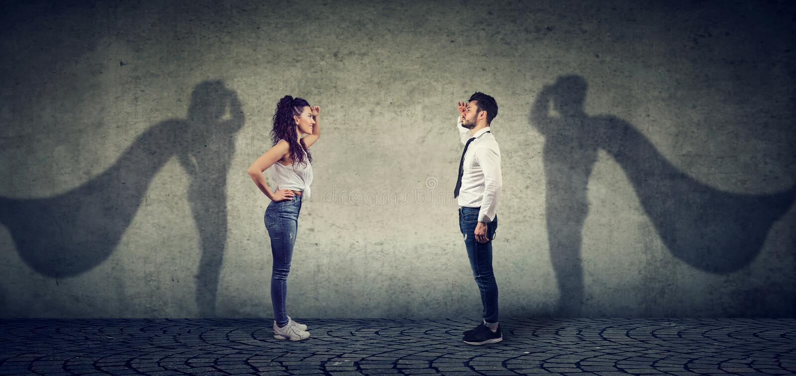 Brave man and woman posing as super hero. Side view of a men and women imagining to be a super hero looking aspired royalty free stock photos