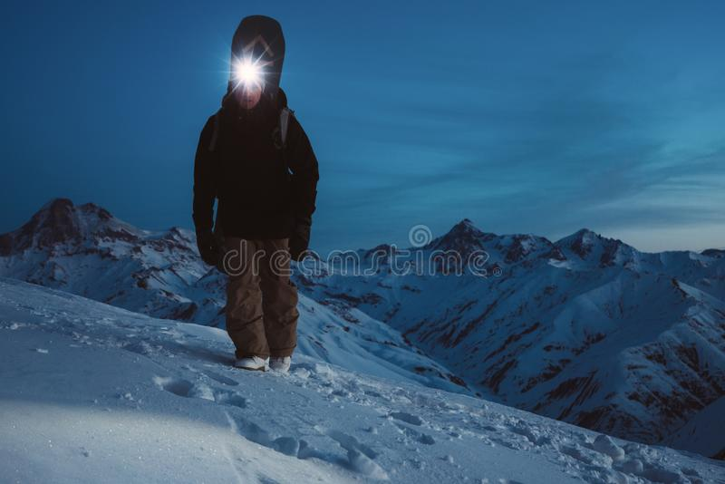 Brave night explorer climb on high mountain. Wearing headlamp, backpack and ski wear. Snowboarder with a snowboard behind his back stock images
