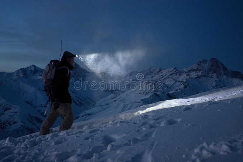 Brave night explorer climbs on high snowy mountains and lights the way with a headlamp. Extreme expedition. Ski tour. Snowboarder. Commit climb on winter slope royalty free stock images