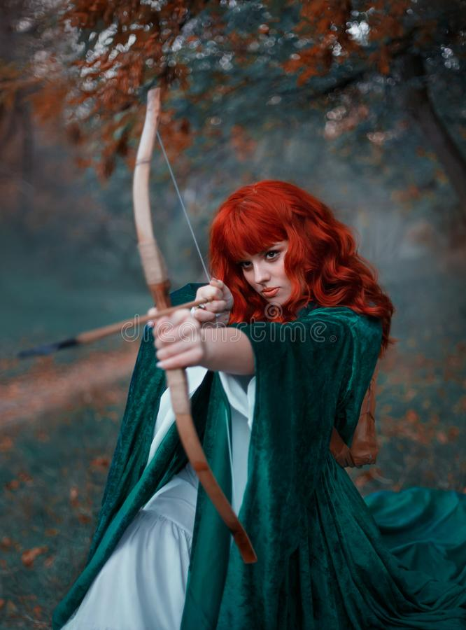 Brave red-haired girl holds a bow in her hands, directing an arrow, experienced hunter goes into battle, warlike image royalty free stock photos
