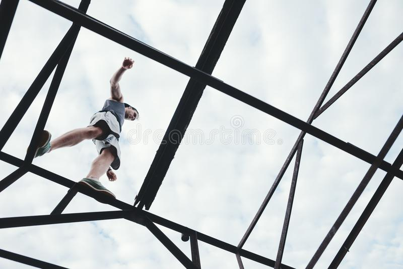 Brave and risky man balancing on the top of high metal construction. Outdoors stock photos