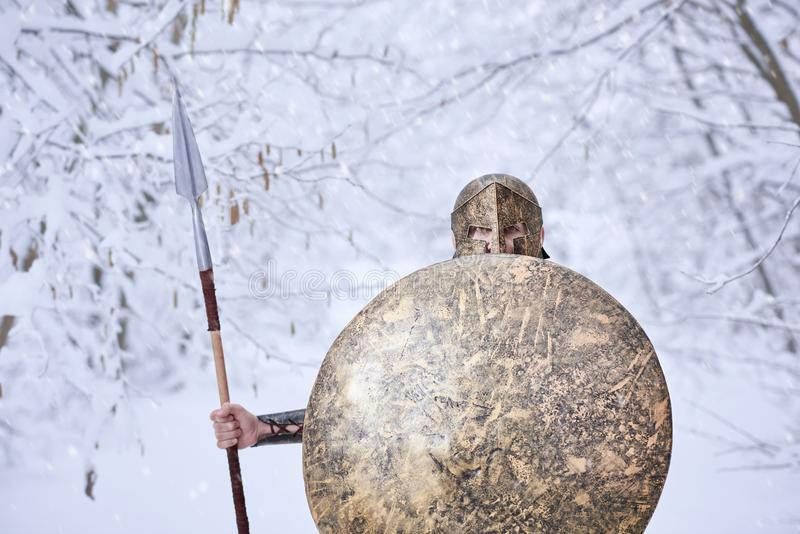 Brave spartan warrior in snowy wood. Warrior from Sparta keeps big round metallic shield in one hand and sharp spear in another. He has traditional metallic royalty free stock photography