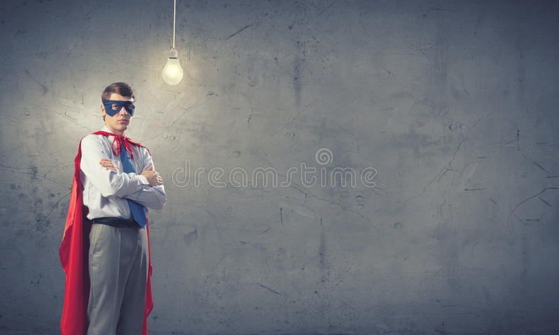 Brave super hero. Young confident super guy in mask and cape royalty free stock images