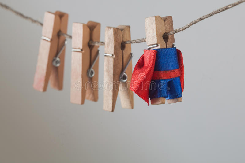 Brave superhero with wooden clothespins team friends. Clothespin leader character in blue suit red cape. gray gradient royalty free stock photography