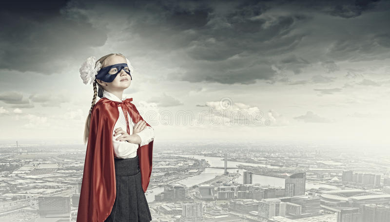 Brave superkid. Cute girl of school age in superhero costume stock images