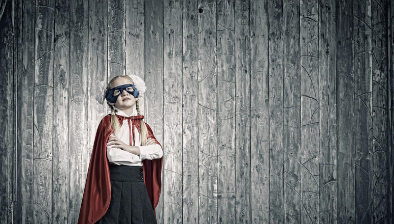 Brave superkid. Cute girl of school age in superhero costume royalty free stock images