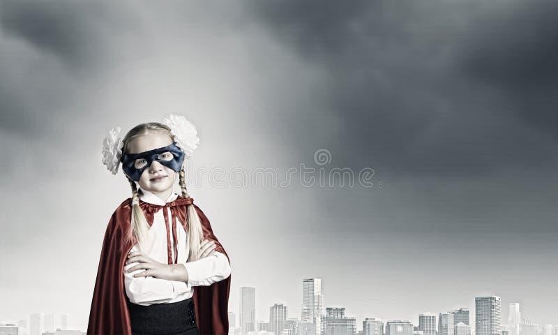 Brave superkid. Cute girl of school age in superhero costume royalty free stock image