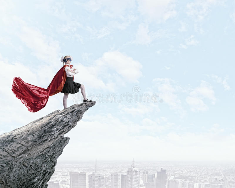 Brave superkid. Cute girl of school age in superhero costume stock photos