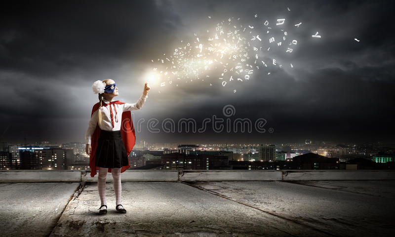Brave superkid. Cute girl of school age in superhero costume with balloon in hand royalty free stock photography