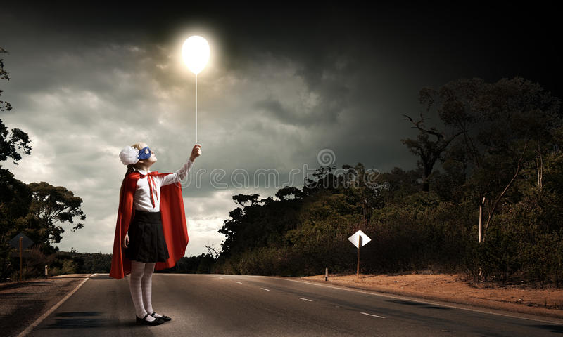 Brave superkid. Cute girl of school age in superhero costume with balloon in hand stock photo