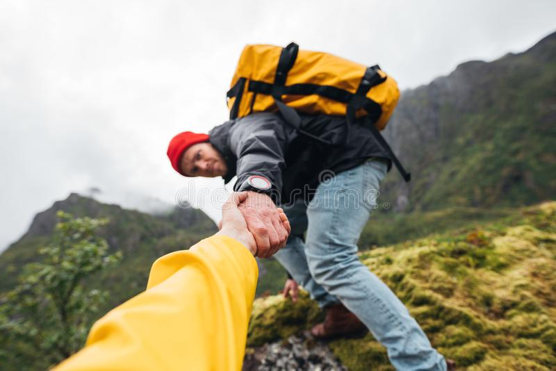 Brave traveler hold hand his friend for helping climb to mountain lifestyle outdoor journey. Group of two active tourist with backpack climb to rock helping each royalty free stock photography