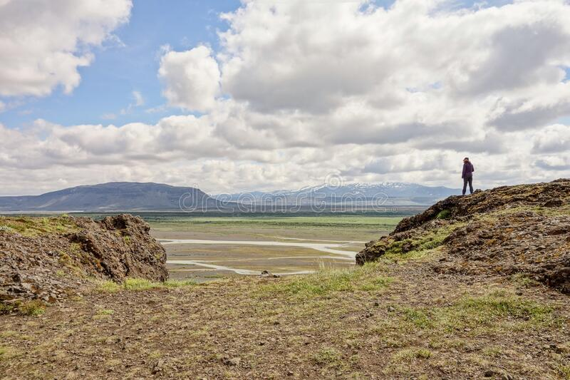 A brave unrecognizable woman facing her fear at Gaukshofdi Panoramic Lookout in Iceland royalty free stock photography