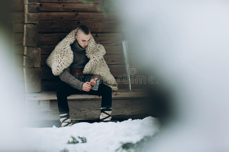 Brave viking warrior sharpening axe before battle in the north, royalty free stock image
