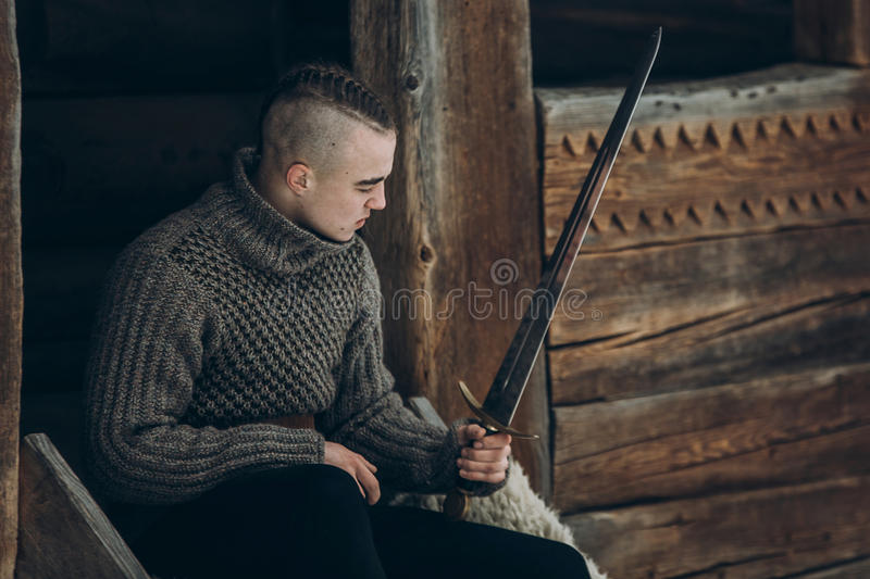 Brave warrior holding sword near historical wood castle building. In winter woods in Scandinavia, handsome viking with mohawk posing with weapon before battle royalty free stock images